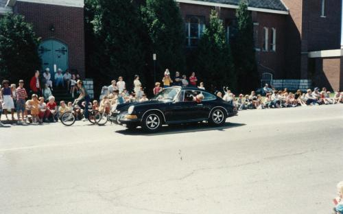 Cassells St Parade in summer of 1987, 2 year old Andrea Parolin performing a technical inspection on the left rear wheel of the 1969 Porsche 911S, on the fly.