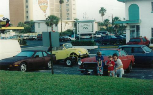 "Again, before of the days of the internet, a dealer would have to buy cars in person at auctions. Sometimes this meant driving to Florida to buy cars! Depicted in front of the Volvo P1800 is: Jayme Parolin (long shorts), Jon Parolin (short shorts) and Terry's long-time friend Ian Shago (mullet). This particular ""Florida run"" saw Terry at the wheel of a 1985 Porsche 944, Joanne 4-wheel towing a 1969 Volvo P1800 with a wood paneled Chevy caprice wagon. Ian handled the Volvo 240 towing the beetle cabriolet."