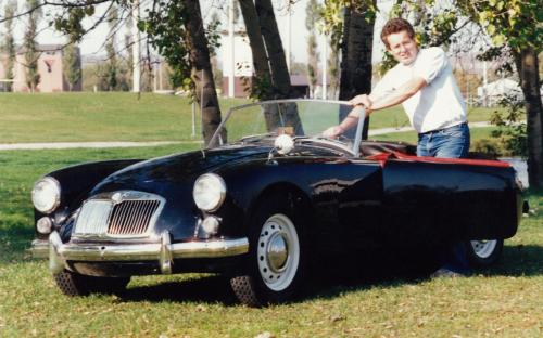Terry Parolin posing with a 1959 MGA roadster next to Thompson Park in North Bay. At the core his business and a driver of its success, is an unbridled enthusiasm for the European automobile. Circa mid-80s.